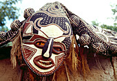 BOTSWANA, Africa, a ceremonial mask hanging near the entrance of a mud hut, Okavango Delta