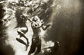 USA, California, man and women swimming underwater in the Forks of Salmon River (B&W)