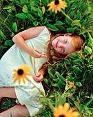 USA, California, portrait of smiling girl lying in the grass and flowers