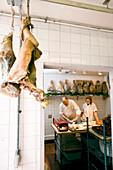 USA, California, chef with meat in kitchen, Eccolo Restaurant, Berkeley