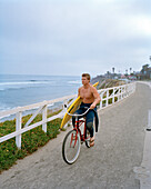 USA, California, Surfer biking with his surfboard on the boardwalk at Pleasure Point, Santa Cruz