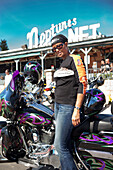 USA, California, Malibu, a biker stands next to her motorcycle in front of Neptunes Net Restaurant on the Pacific Coast Highway