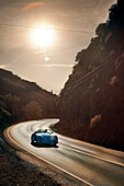 USA, California, Malibu, an old Porche drives along Mulholland Drive in the Malibu hills