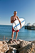 USA, California, Malibu, former Malibu mayor and the owner of Zuma Jay surf shop Jefferson Wagner stands with his surfboard by the Malibu Pier, Surfrider Beach