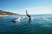 USA, California, Malibu, El Pescador Beach, an athletic woman dives off of her paddleboard into the Pacific Ocean