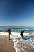 USA, California, Malibu, paddleboarders walk their boards down to the water at Zuma Beach