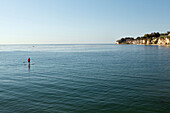 USA, California, Malibu, a man paddleboards in Paradise Cove, a view to the North