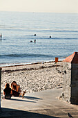 USA, California, Malibu, young women carry on a conversation at Surfrider Beach, the Malibu Pier