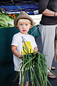 USA, California, Malibu, a young boy holds produce for his mom at the Malibu farmers market on Civic Center Way