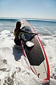 USA, California, Malibu, El Pescador Beach, an athletic woman carries her paddleboard into the Pacific Ocean