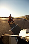 USA, California, Malibu, a couple on a motorcycle cruises along the Pacific Coast Highway at the end of the day