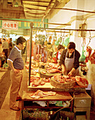 CHINA, Hangzhou, customer and butcher at local market