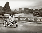CHINA, Guilin, couple traveling on motorcycle in rural Guilin (B&W)