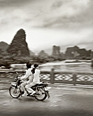 China, Guilin, people traveling in motorbikes on bridge with mountains in the background (B&W)