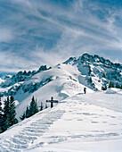 USA, Colorado, Skier hiking up the mountain to ski expert terrain, Telluride Ski Resort