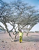 ERITREA, Gelallo, Abdu Bedri standing under an Acacia tree in his village