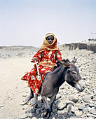 ERITREA, Foro, A Bedouin girl rides side-saddle on a donkey and tends to her livestock