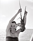 FIJI, Northern Lau Islands, a young woman holds up a freshly caught spiny lobster (B&W)