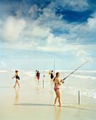USA, Florida, women fishing on beach, New Smyrna Beach