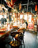 USA, Florida, man sitting at bar, Aj's Seafood Restaurant, Destin