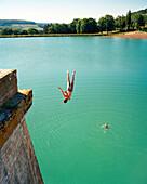 FRANCE, Burgundy, man doing backflip into reservoir, Aubigny Les Sombrenon