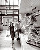 FRANCE, Burgundy, woman shopping at the local butcher, Dijon (B&W)