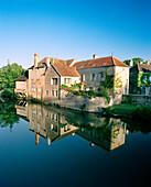 France, Burgundy, building reflecting on lake, Noyers