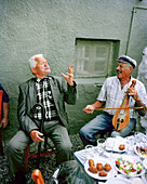 GREECE, Patmos Island, Michalis playing the lyra and while his friend sings at Diakofti Taverna, Early Afternoon