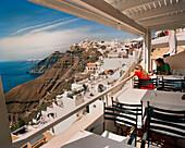 GREECE, Santorini, Fira, a tourist couple enjoys a drink and the view high above the Mediterranean Sea on the island of Santorini