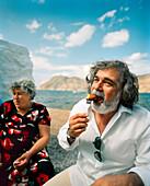 GREECE, Patmos, Diakofti, Dodecanese Island, Kostas enjoys a zucchini ball at Taverna Diakofti by the Agean Sea, the island of Patmos