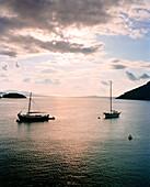 GREECE, Patmos, Grikos, Dodecanese Island, boats anchored in Grikos Bay at sundown, the Agean Sea