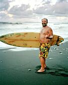 USA, Hawaii, portrait of senior surfer giving the hang loose, The Big Island, Honoli'i Beach