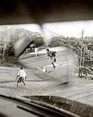 HONDURAS, Roatan, young teenagers playing soccer game (B&W)