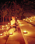 INDIA, Jaipur, woman sitting with lit candles on steps, Oberoi Rajvilas Hotel
