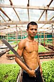 INDONESIA, Mentawai Islands, Kandui Surf Resort, portrait of young man holding machete