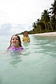 INDONESIA, Mentawai Islands, Kandui Surf Resort, girls playing in the ocean with palm trees in the background