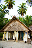 INDONESIA, Mentawai Islands, Kandui Surf Resort, surfboards stored under a thatched roof hut