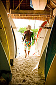 INDONESIA, Mentawai Islands, Kandui Resort, rear view of a man carrying surfboards out of the board storage room