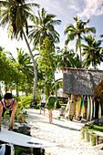 INDONESIA, Mentawai Islands, men and woman walking outside Kandui Resort