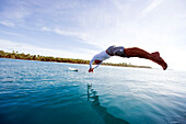 INDONESIA, Mentawai Islands, Kandui Resort, surfer diving into the water to go surfing, Nipussi