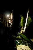 INDONESIA, Mentawai Islands, Kandui Resort, musician playing guitar in a beachside hut at night