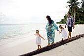 INDONESIA, Mentawai Islands, Kandui Resort, family walking and balancing on a fallen palm tree