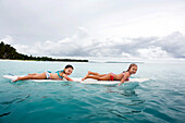 INDONESIA, Mentawai Islands, Kandui Resort, two young girls paddling on a surfboard in the Indian Ocean