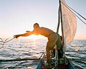 MADAGASCAR, man in pirogue throwing rope, Indian Ocean, Anjajavy