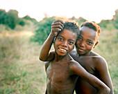 MADAGASCAR, two shirtless Mahafaly boys smiling, portrait, Mahazoarivo Village