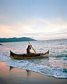 MADAGASCAR, man in dugout canoe at dusk, Jardin Vanille Beach, Nosy Be