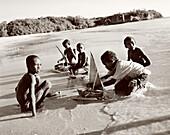 MADAGASCAR, boys playing with toy boats, Anjajavy (B&W)