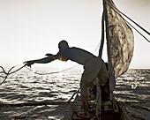 MADAGASCAR, Anjajavy, fisherman in pirogue throwing a rope at dusk