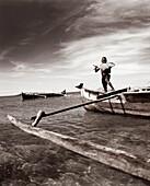 MADAGASCAR, Nosy Komba, Jardin Vanille, boy holding a Travali fish standing on an outrigger canoe, Indian Ocean