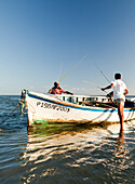 MAURITIUS, fishermen pull their rods out of a boat after a day of fishing, Bel Ombre, Indian Ocean